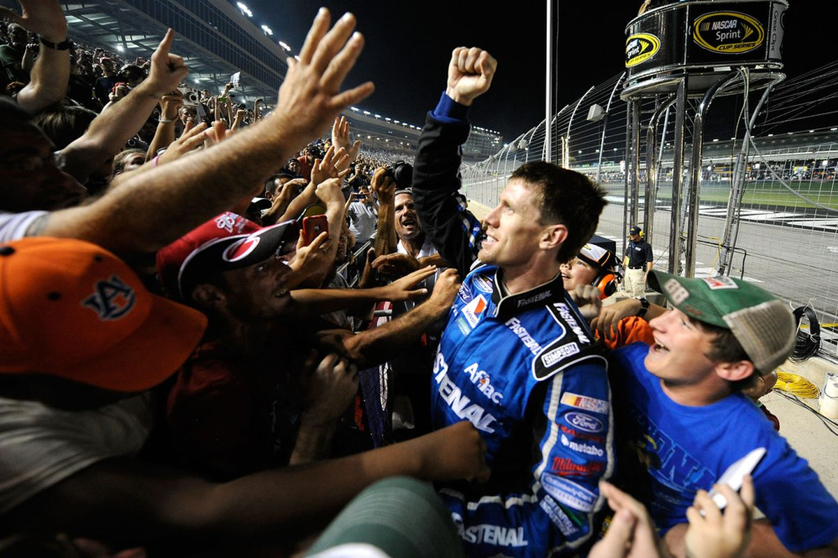 Carl Edwards celebrates in the stands after winning the NASCAR Nationwide Series Great Clips 300 at Atlanta Motor Speedway.