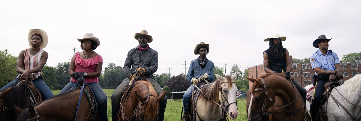 Six Black riders sit astride horses, with a public housing building visible in the background.