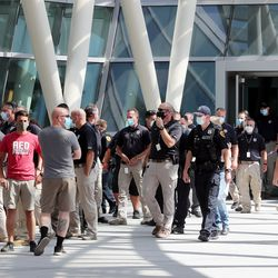 Salt Lake police officers, some with their families, walk out of the Public Safety Building on Monday, Aug. 10, 2020, to listen a statement from the Salt Lake Police Association rejecting Mayor Erin Mendenhall's claim of racial and social disparities across all Salt Lake City agencies and institutions.