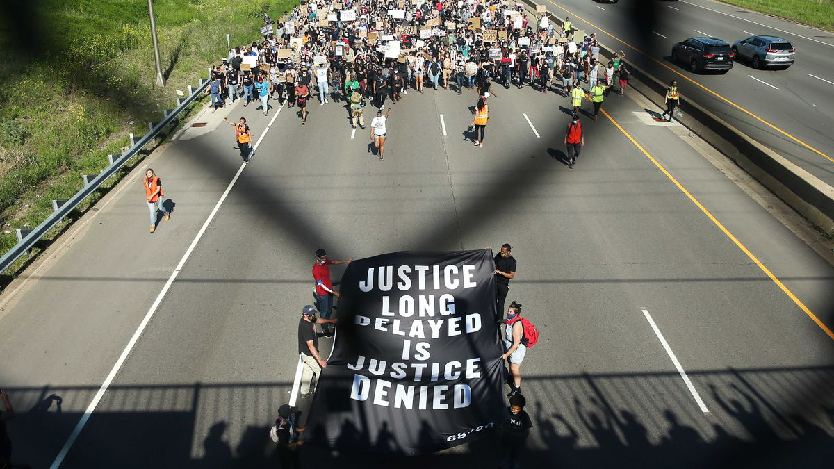 "A crowd of demonstrators headed by a sign that reads, ""Justice long delayed is justice denied,"" blocks all the lanes of a highway."