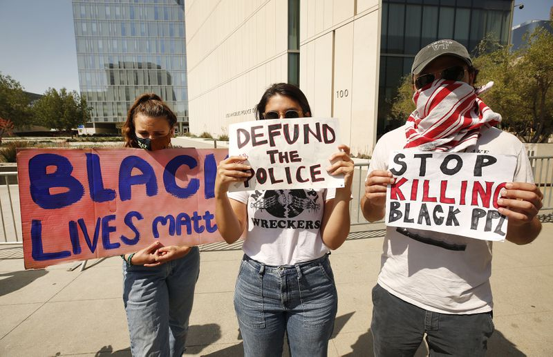 "Protesters hold signs reading, ""Black lives matter,"" ""Defund the police,"" and ""Stop killing black ppl."""