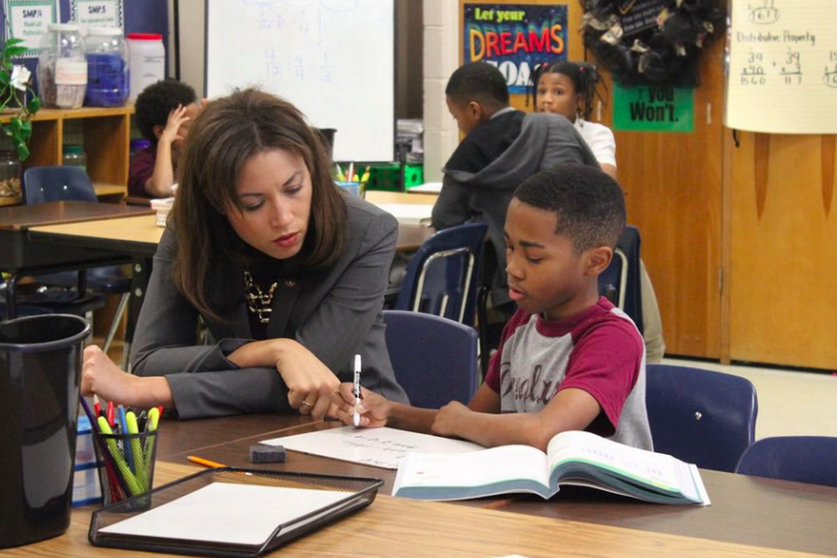 Penny Schwinn looks at classwork with a student in Memphis in February, soon after becoming Tennessee's education commissioner.