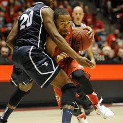 Utah Utes guard Brandon Taylor (11) drives to the basket around Brigham Young Cougars guard Anson Winder (20) during a game at the Jon M. Huntsman Center on Saturday, December 14, 2013.