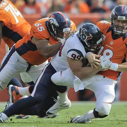 Denver Broncos quarterback Peyton Manning (18) is sacked by Houston Texans defensive end J.J. Watt (99) as guard Manny Ramirez (65) defends in the third quarter of an NFL football game Sunday, Sept. 23, 2012, in Denver.
