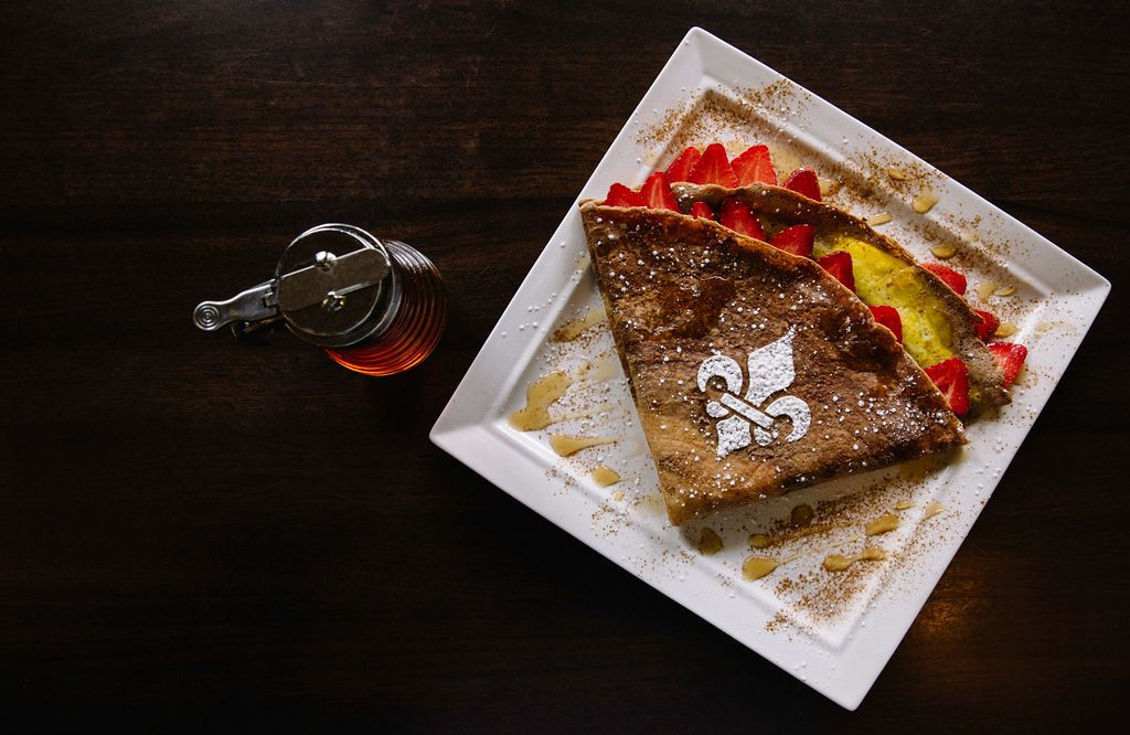A sweet crepe packed with fruit and sprinkled with cinnamon sits atop a square white plate on a black table. The crepe is adorned with a powdered sugar fleur-de-lis.
