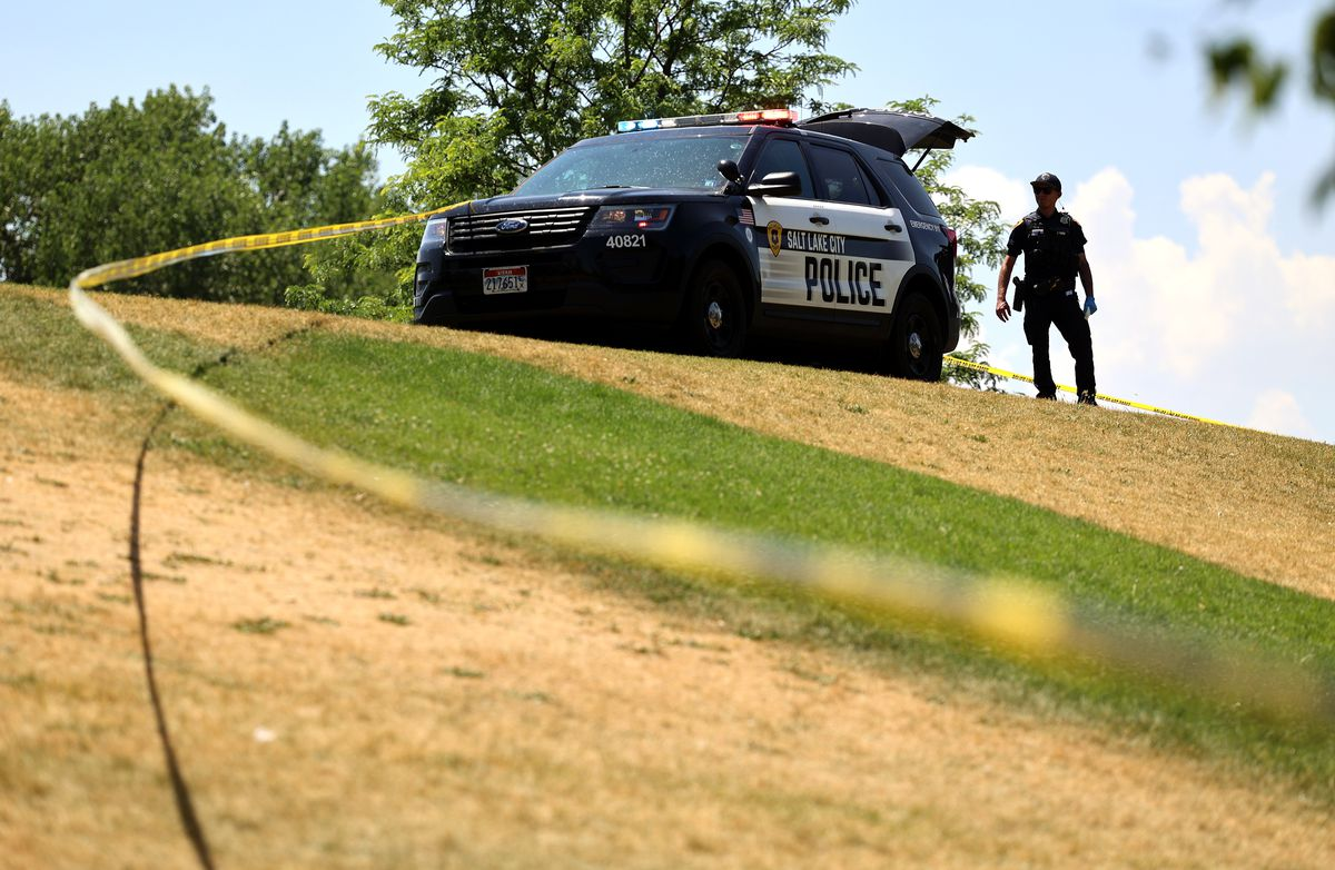 A Salt Lake police officer watches as others investigate a fatal stabbing at Liberty Park on July 4, 2021.