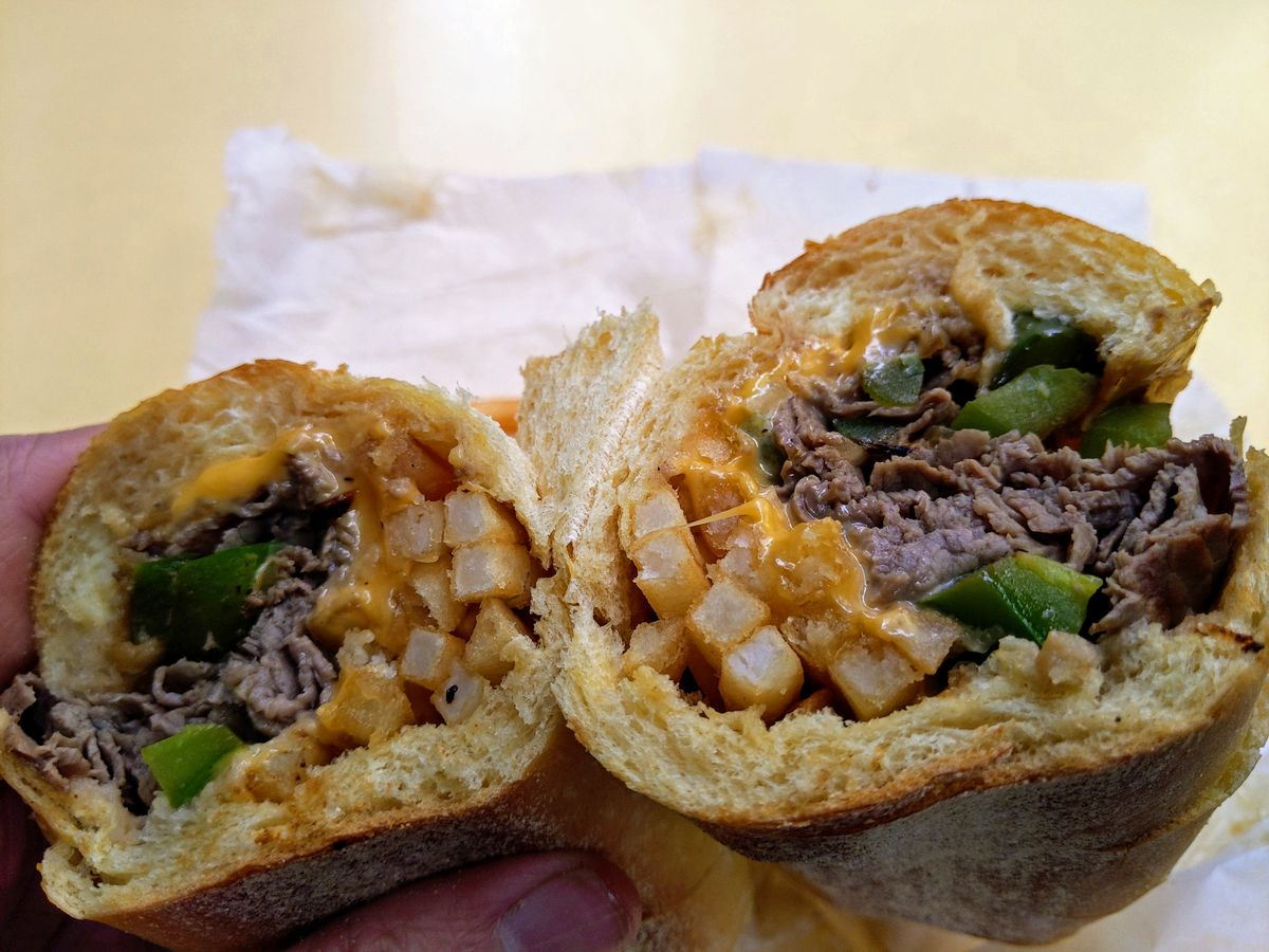 Hero sandwich in cross section showing beef, onions, green peppers, and french fries.