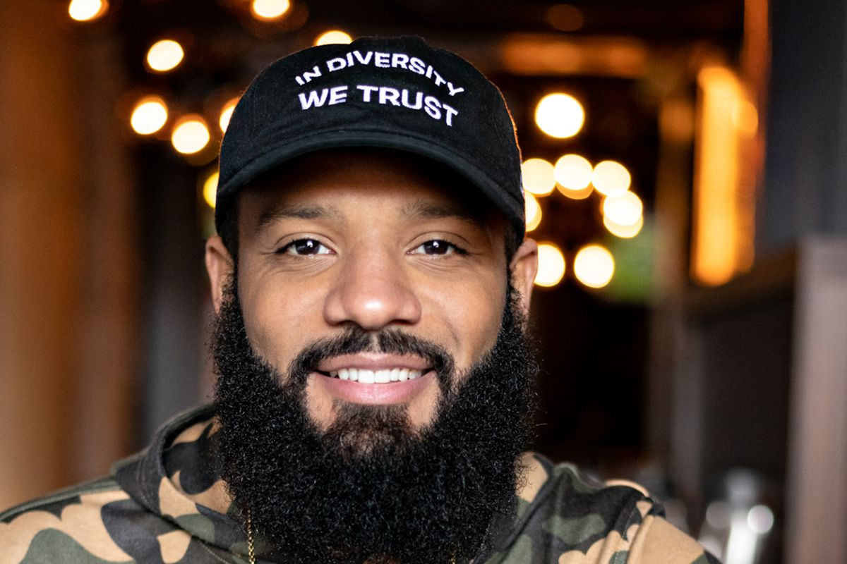 """Justin Sutherland smiling and leaning on a banquet, wearing a black hat with white stitching that says, """"In Diversity We Trust."""""""