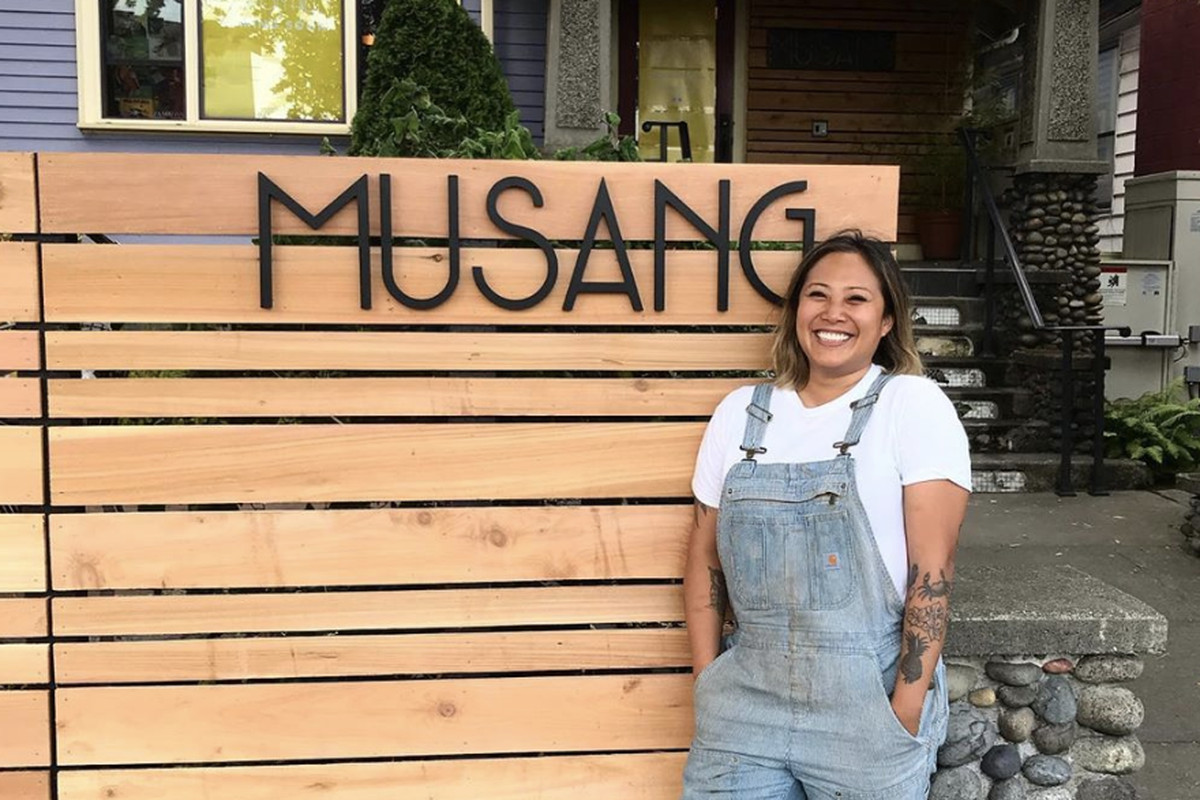 The sign in front of Musang against light wood, with chef Melissa Miranda standing next to it.