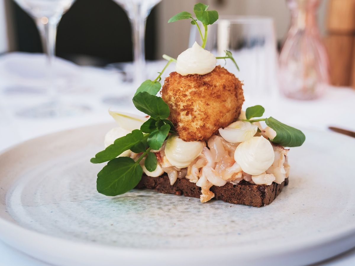 Smørrebrod toast topped with seafood, fried egg, and herbs, on a white plate sitting on a set table