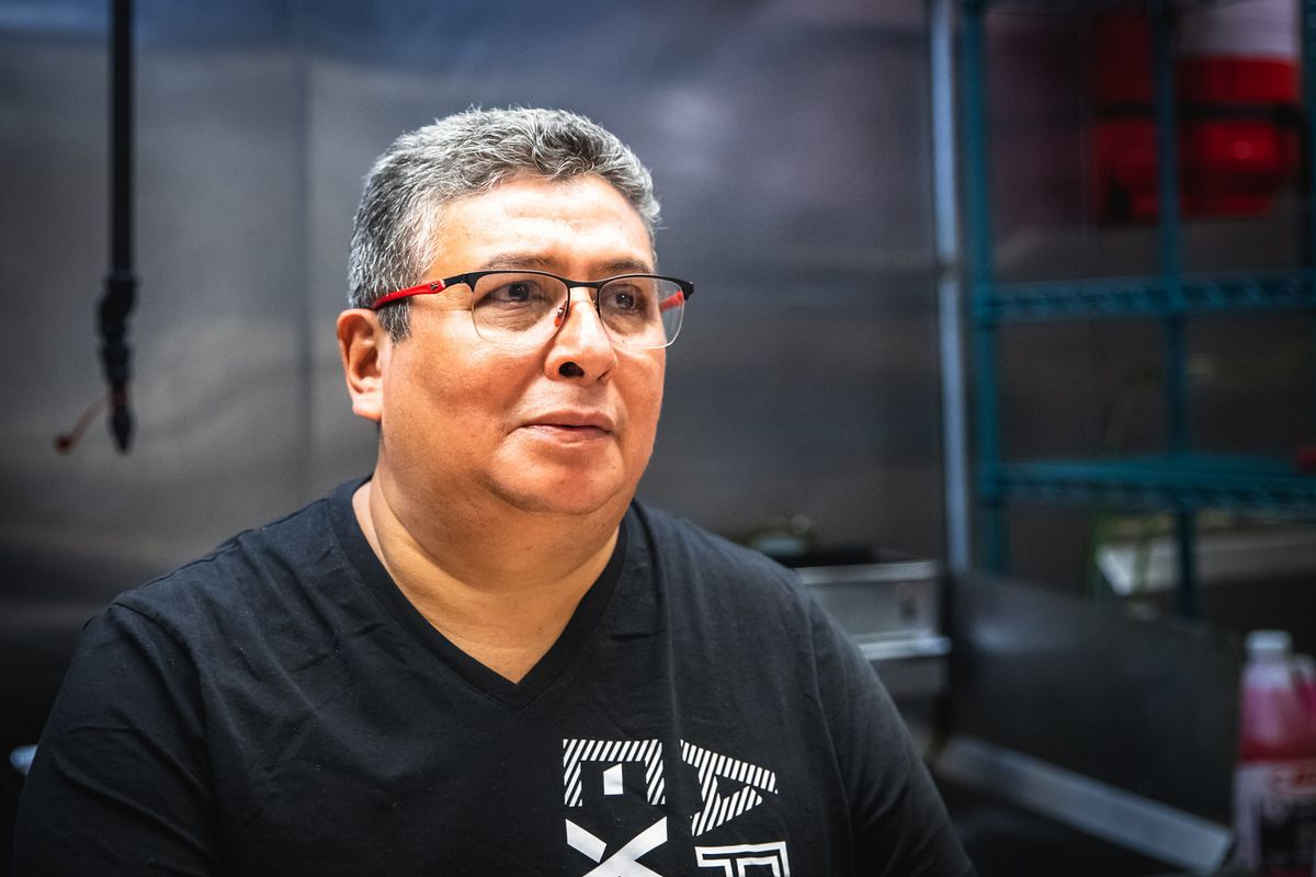 A person wearing glasses and a black T-shirt while inside a kitchen.