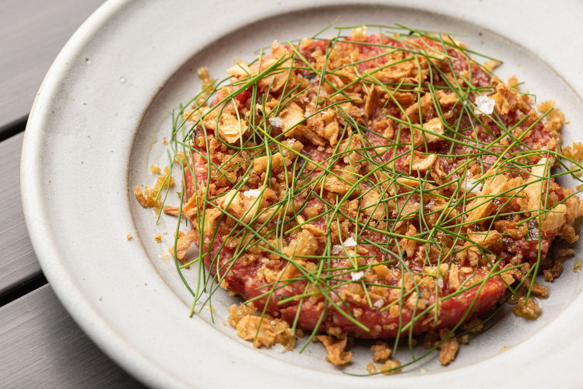 A wide raw meat tartare on a plate.