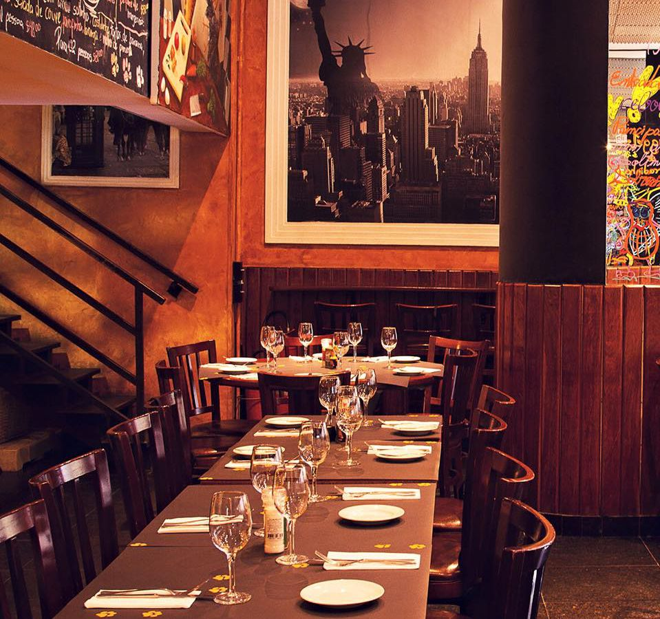 A restaurant interior with tables set for dinner, an iron stairway off to one side, a large image of a city skyline on the back wall, and wood accents around