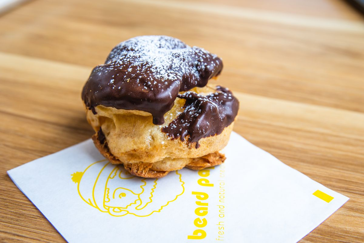 A small cream puff topped with chocolate icing and powdered sugar