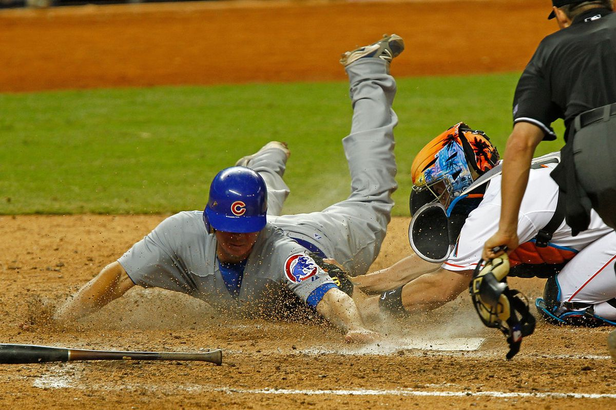 Steve Clevenger of the Chicago Cubs slides into home safely as John Buck  of the Miami Marlins applies the tag during a game at Marlins Park in Miami, Florida.  (Photo by Mike Ehrmann/Getty Images)