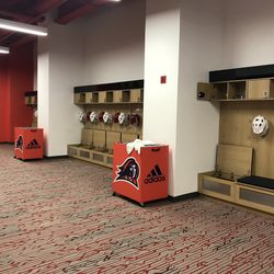 Another angle of the men's lacrosse locker room, which includes a TV and whiteboard. The TV has closed-circuit access to watch other NJIT sports.