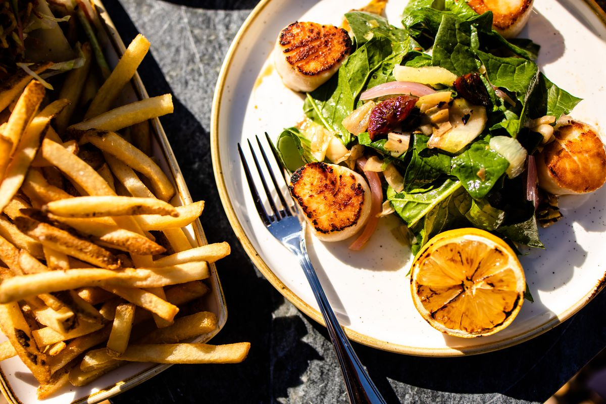 Seared scallops on a bed of salad with French fries next to it