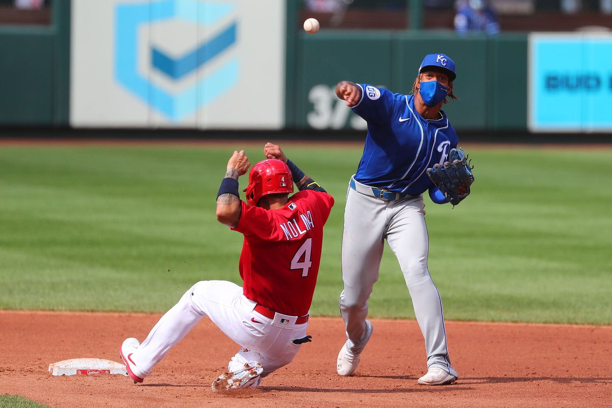 Adalberto Mondesi #27 of the Kansas City Royals turns a double play over Yadier Molina #4 of the St. Louis Cardinals in the fourth inning at Busch Stadium on July 22, 2020 in St Louis, Missouri.