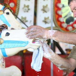 Evencio Gutierrez washes the carousel in preparation for the Utah State Fair at the Utah State Fairpark in Salt Lake City on Wednesday, Sept. 4, 2013. The fair runs Sept. 5-15.