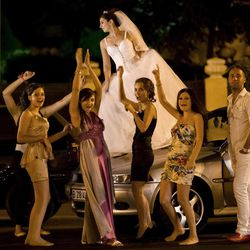 In this Sunday, Aug. 26, 2012 photo shot under iodine street lighting, a Romanian bride dances on a car at the Triumph Arch in Bucharest, Romania. The arch, a replica of the Arc de Triomphe in Paris, the French capital, is a rendezvous place for brides on the wedding night for the bride stealing ritual. The ancient Romanian tradition of bride stealing is getting bigger, brasher and an increasingly common sight in the Romanian capital, the region's undisputed party town.