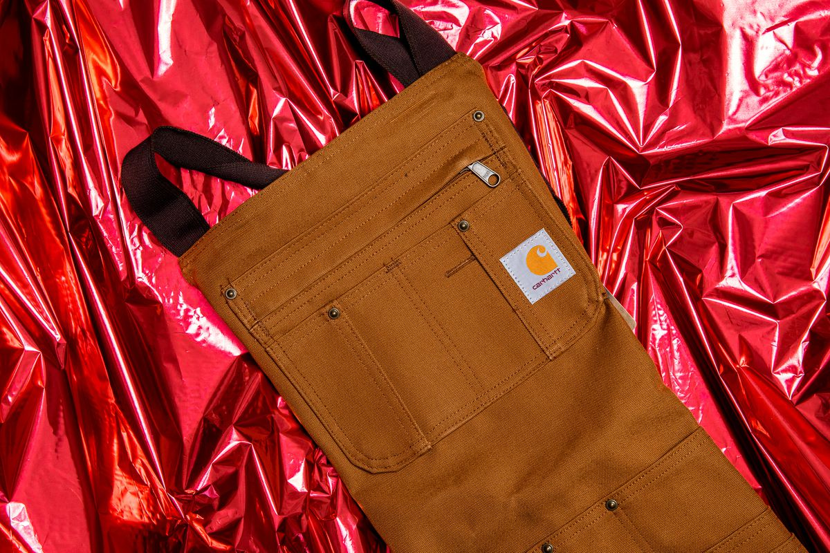 A brown fabric apron with zippers and a carhartt logo.