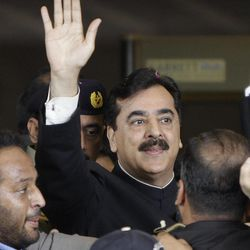 Pakistani Prime Minister Yousuf Raza Gilani, center, waves upon his arrival at the Supreme Court for a hearing in Islamabad, Pakistan, Thursday, April 26, 2012.  The Supreme Court convicted Gilani of contempt on Thursday for refusing to reopen an old corruption case against President Asif Ali Zardari on Thursday, but spared him a prison term in a case that has stoked political tensions in the country.