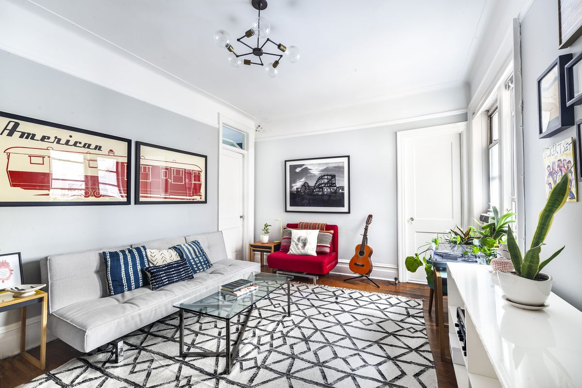 A living area inside a Brooklyn Heights apartment with hardwood floors, a light grey couch, a glass coffee table, grey walls, and base moldings.