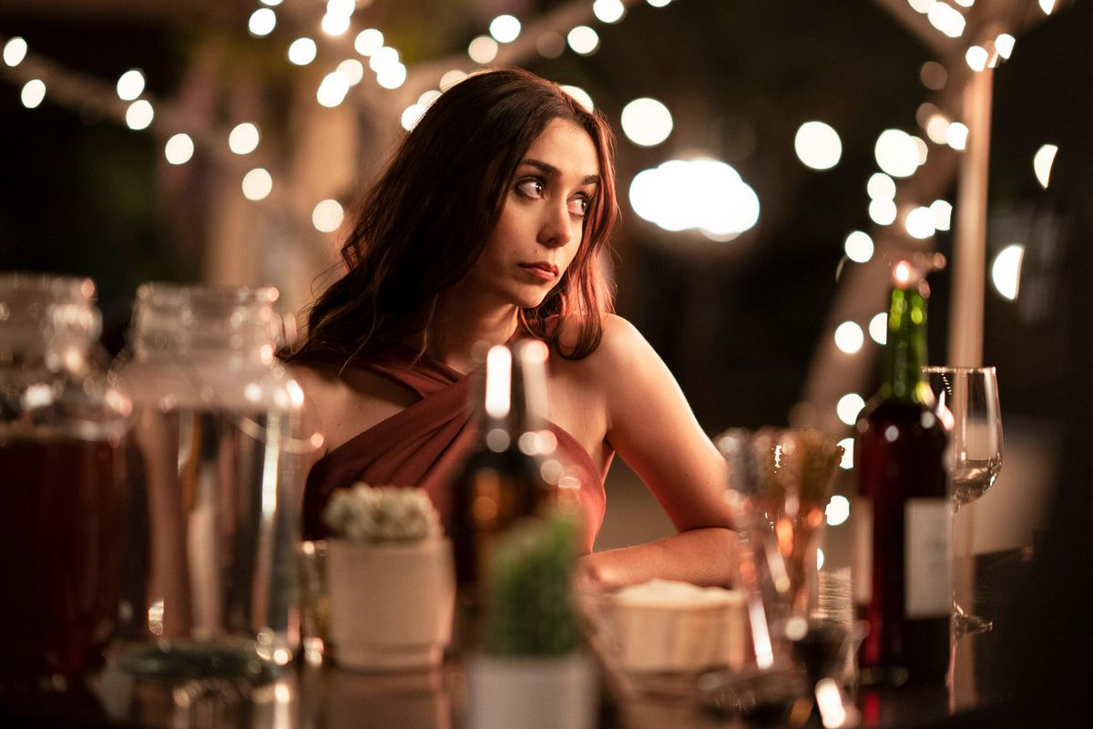 Cristin Milioti, sitting among string lights at a wedding reception, rolls her eyes at something offscreen in Palm Springs.