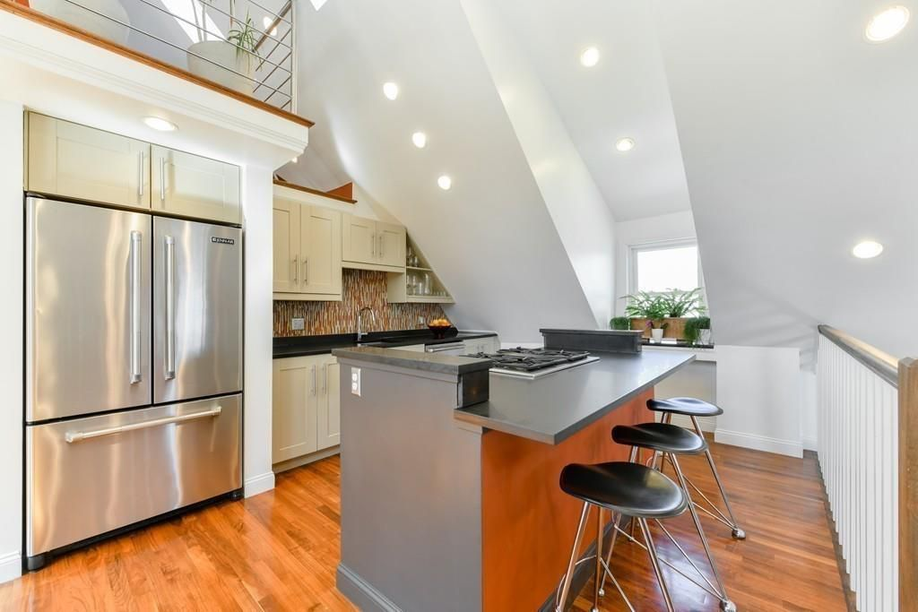 An open kitchen with double-door fridge and an island with three stools in front of it.