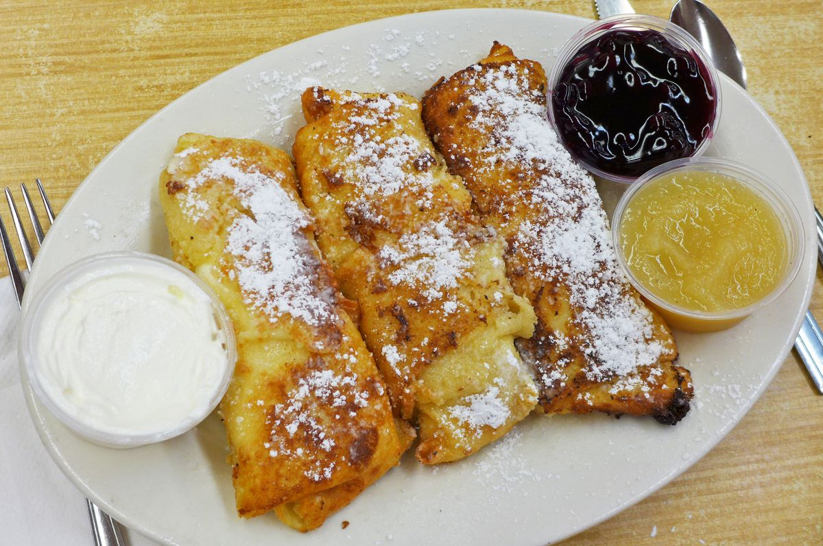 Three nicely browned cheese blintzes are topped with powdered sugar...