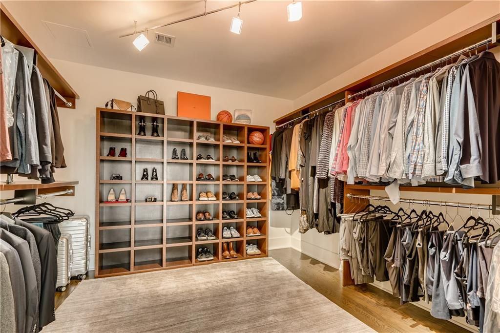 A huge custom master closet with many shoes and shirts.