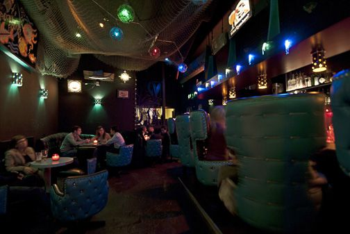 The low-lit interior of Shorty's, with high-backed vintage blue chairs.