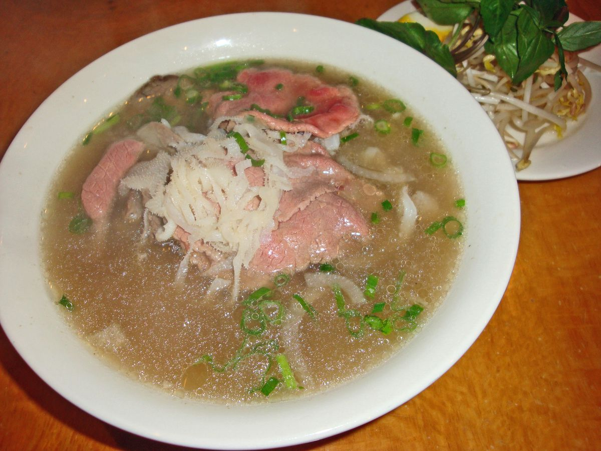A bowl of pho with sliced raw steak floating on top.