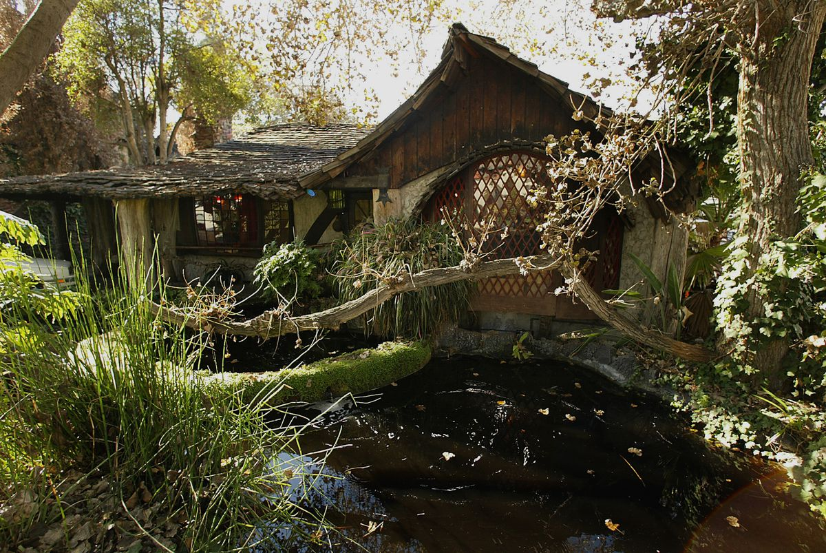 A pond fronts a cottage with a thatched roof and a facade that's partially timbered.