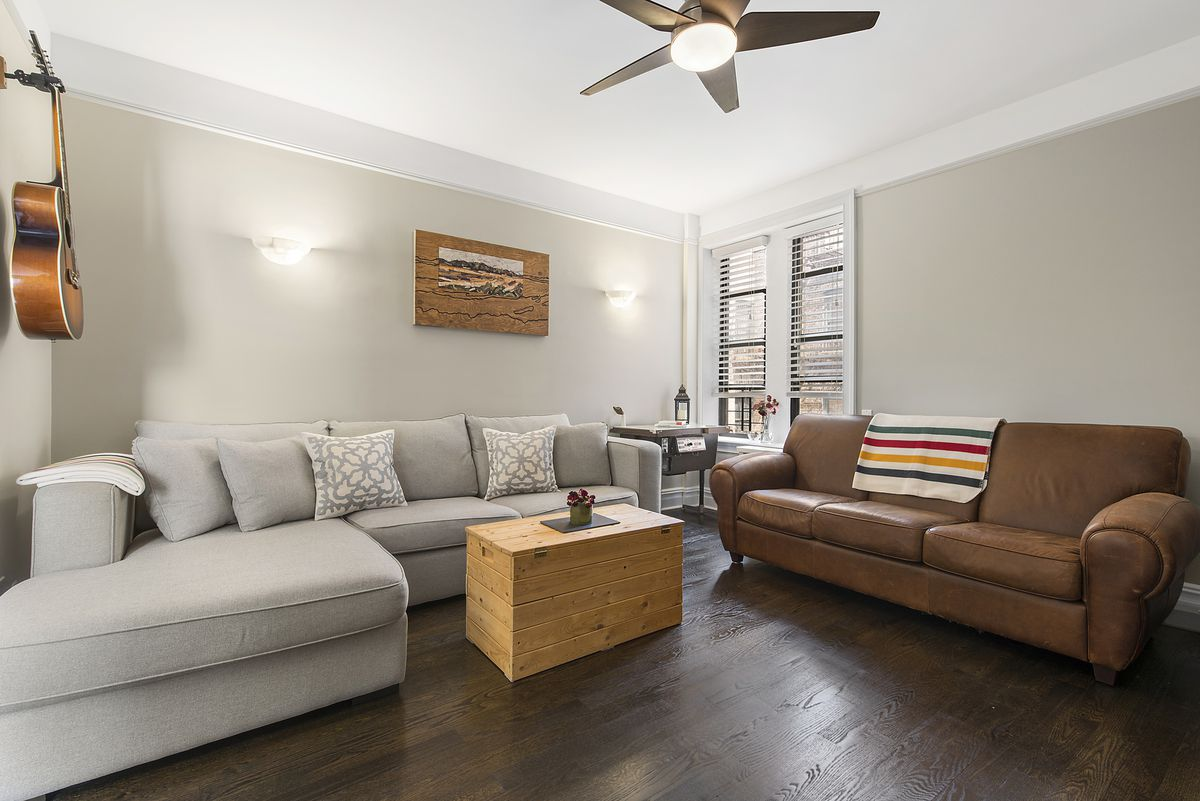 A living area with hardwood floors, beige walls, crown moldings, and a light grey couch.