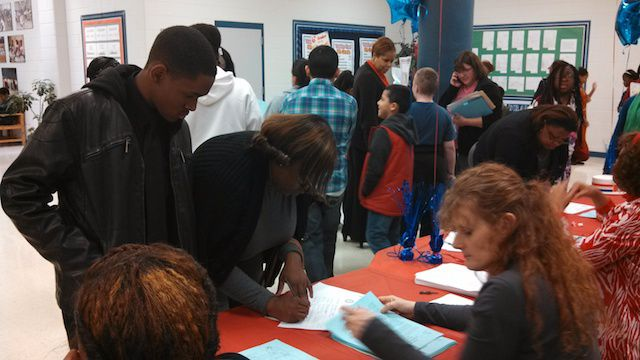 Yolanda Jones and her son, Reginald, sign in at Thursday night's Parent Expo at Colonial Middle School.