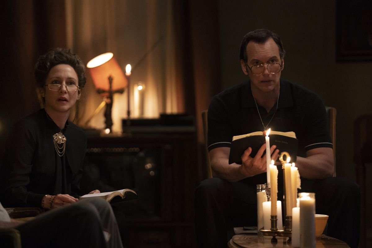 Ed and Lorraine Warren sit with bibles in the candle light in The Conjuring: The Devil Made Me Do It