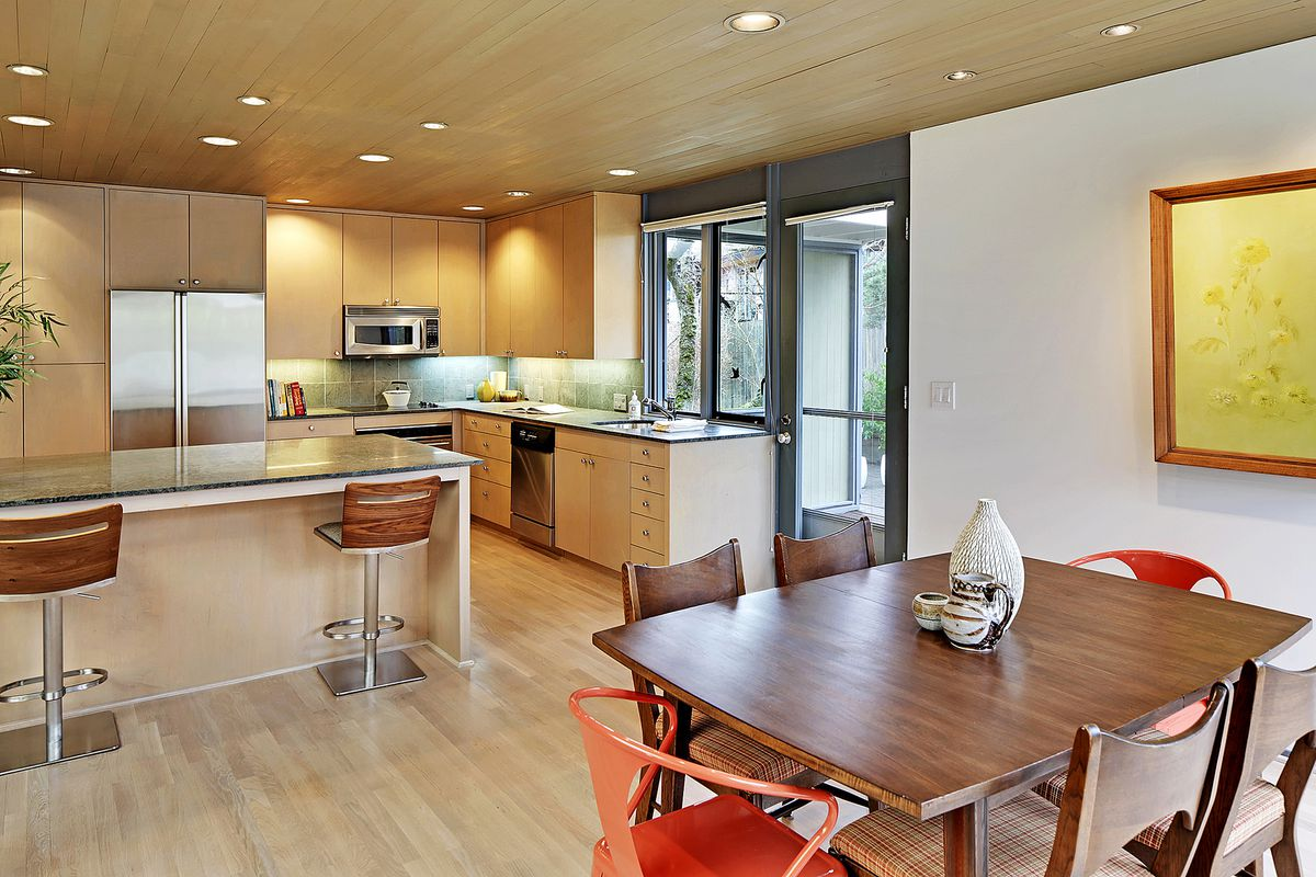 A kitchen (background) and dining area (foreground) with wood beam ceilings and recessed lighting.