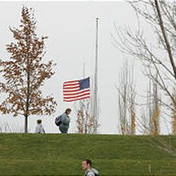 Students at BYU-Idaho walk past the flag flying at half-staff in Rosa Parks' honor on campus in Rexburg, Idaho.