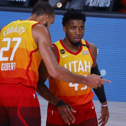 Utah Jazz's Donovan Mitchell, right, talks with Rudy Gobert during the first quarter against the Denver Nuggets in Game 4 of an NBA basketball first-round playoff series, Sunday, Aug. 23, 2020, in Lake Buena Vista, Fla.