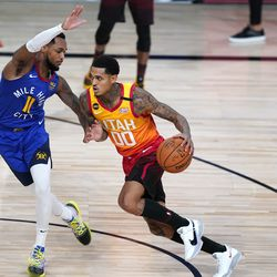 Utah Jazz's Jordan Clarkson (00) drives toward the basket as Denver Nuggets' Monte Morris (11) defends during the first half of an NBA basketball first round playoff game Sunday, Aug. 23, 2020, in Lake Buena Vista, Fla.