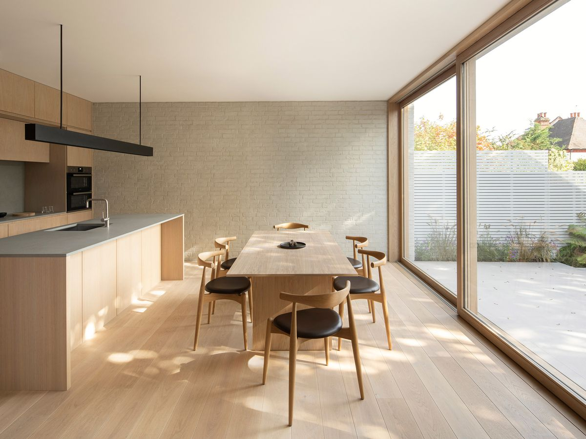 Timber dining table in pale wood kitchen.