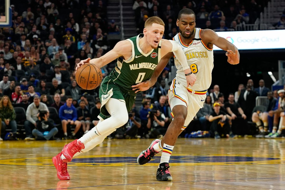 Milwaukee Bucks guard Donte DiVincenzo drives the ball against Golden State Warriors guard Alec Burks during the third quarter at Chase Center.