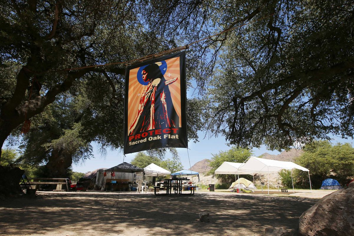 """A flag that says """"Protect Sacred Oak Flat"""" hangs over an encampment belonging to protesters."""