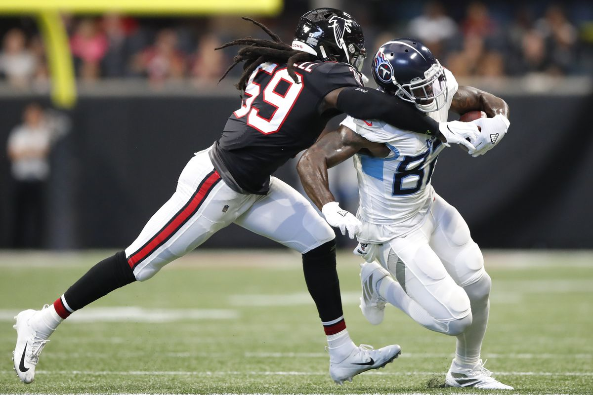 Delanie Walker of the Tennessee Titans is hit by De'Vondre Campbell of the Atlanta Falcons in the first half of an NFL game at Mercedes-Benz Stadium on September 29, 2019 in Atlanta, Georgia.