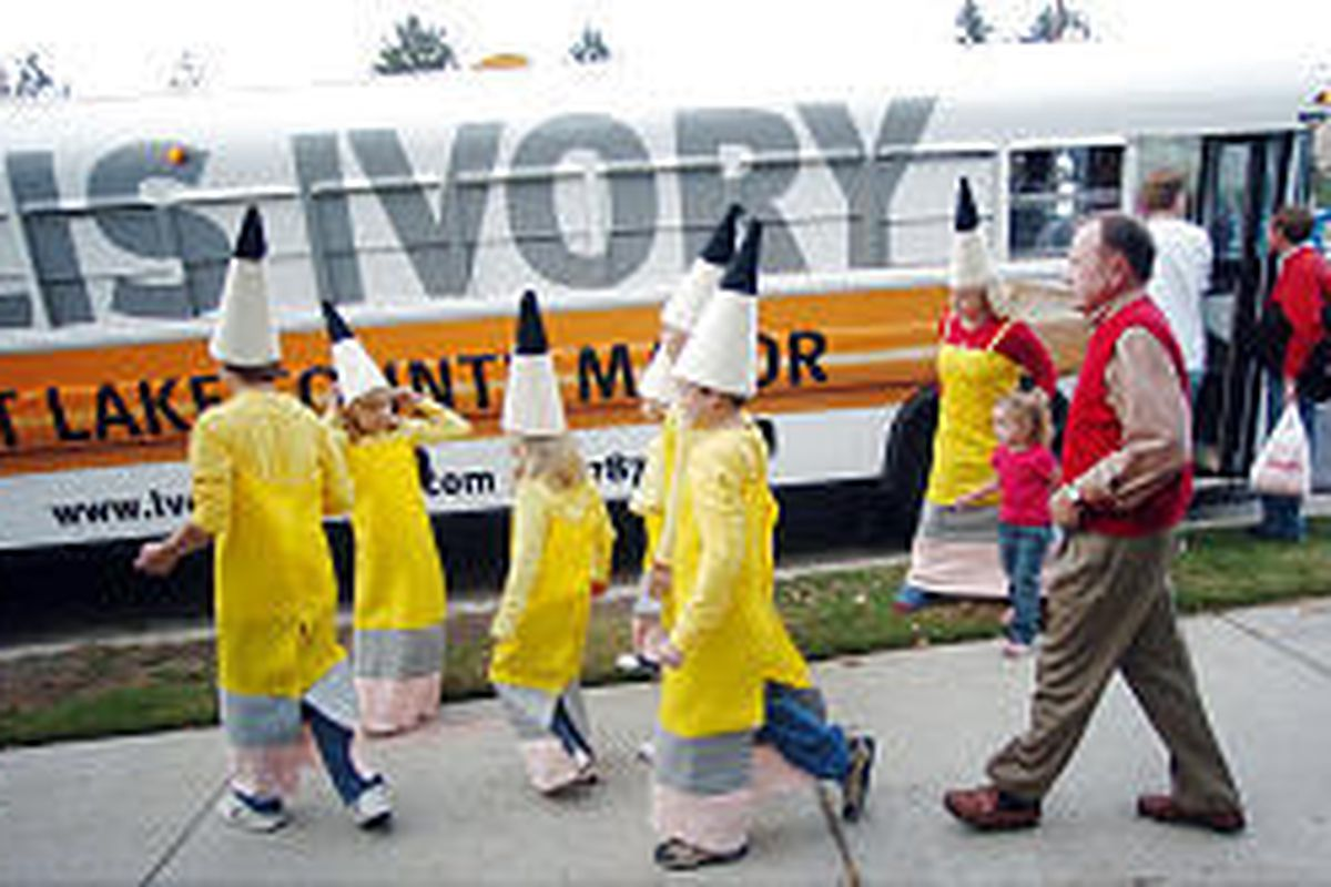 Salt Lake County mayoral candidate Ellis Ivory and his grandchildren walk past an old Granite District school bus made up to be a moving billboard.