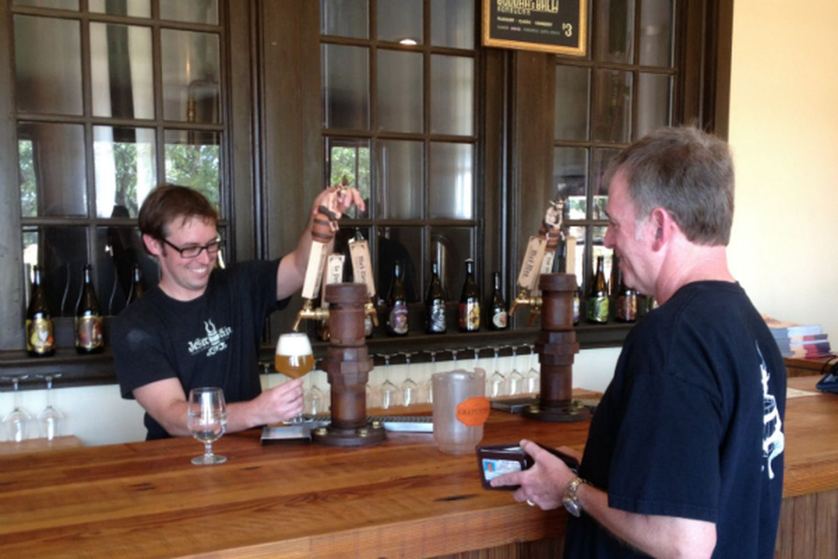 """Jester King's Jeffrey Stuffings serves """"longtime friend of the brewery"""" George Petras."""
