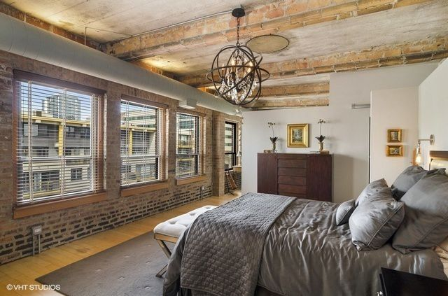 A bedroom with a view outside three large windows. Exposed brick and rustic details.