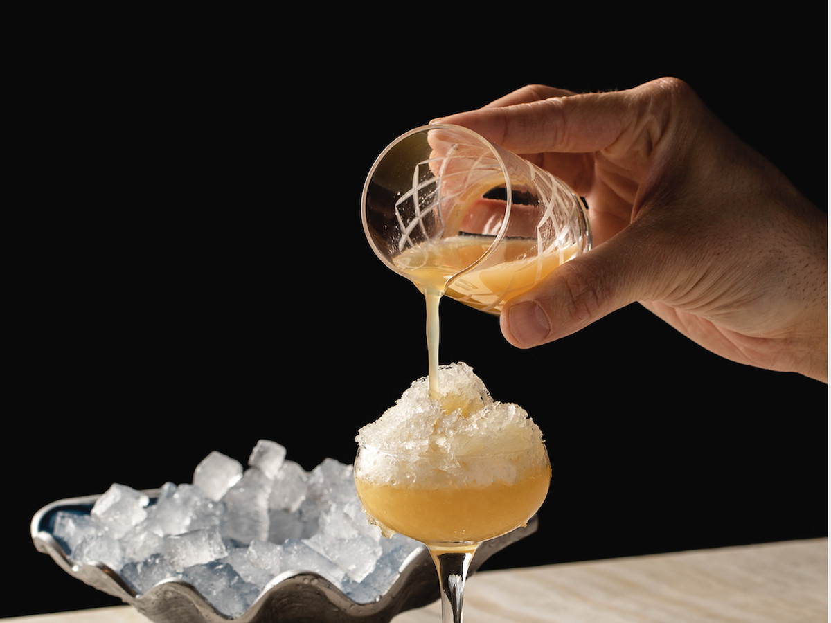 A hand pouring an orange cocktail into a coupe glass.