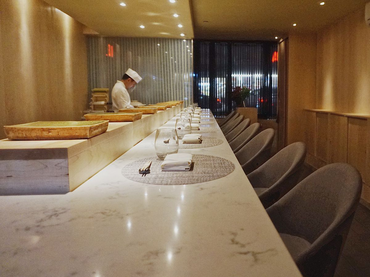 The bar at Koyo which features a marble countertop and oval shaped chairs placed against it